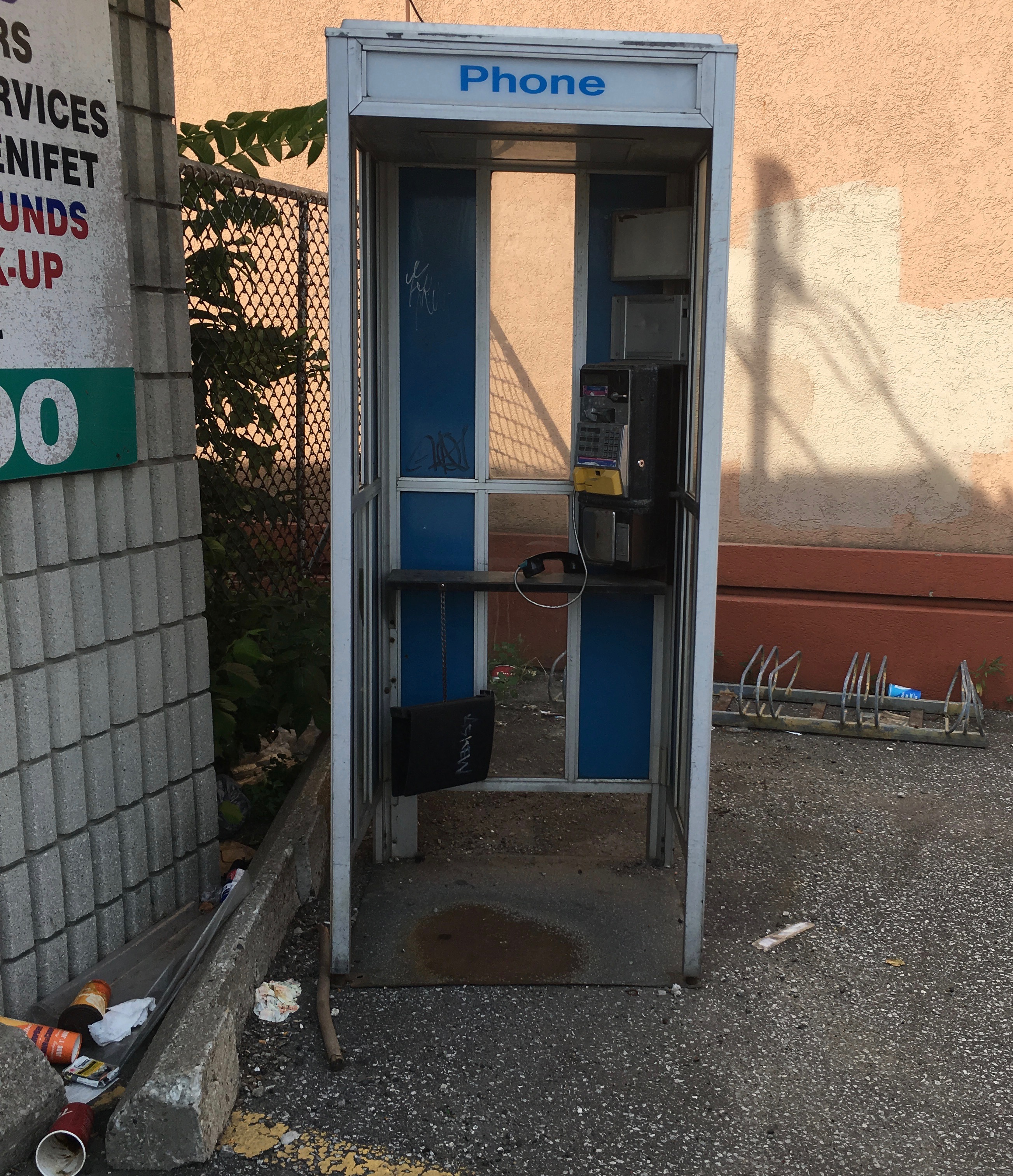 Urine stained phone booth with litter