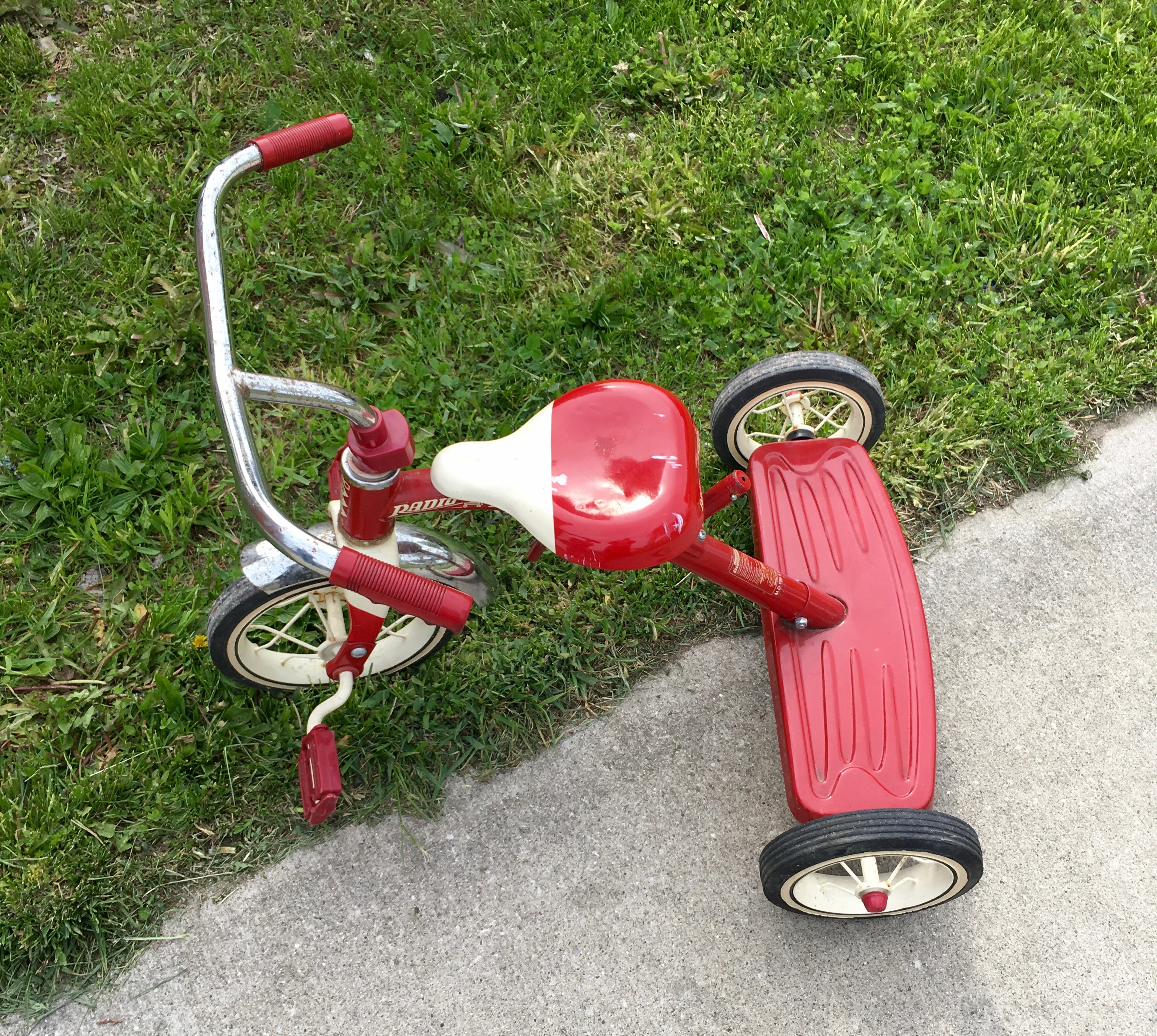 Red and white tricycle on edge of grass