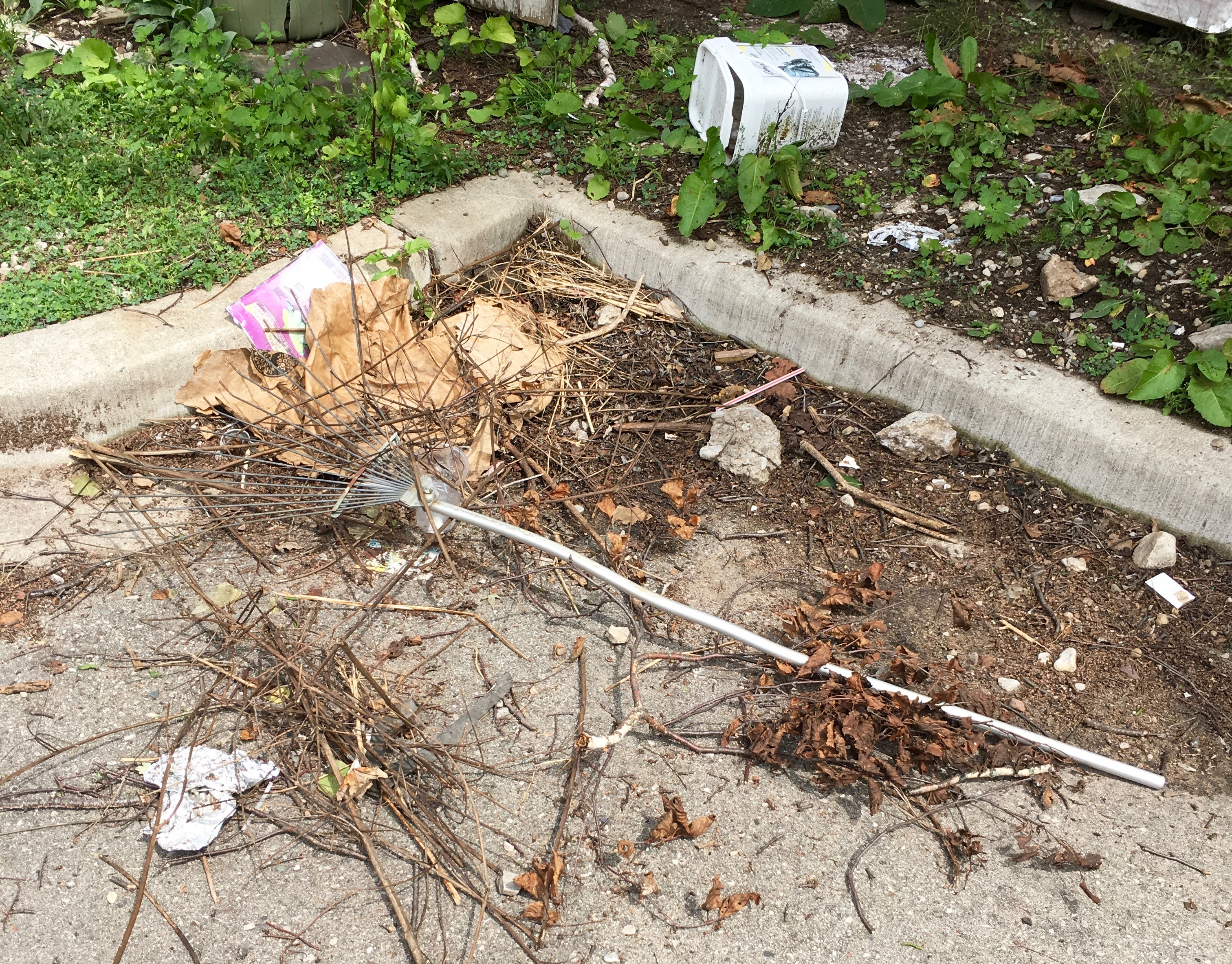 metal rake on concrete under twigs